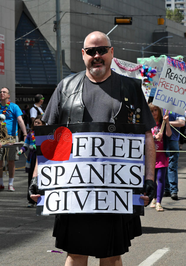 Free Spankings. Man holding up a free spankings sign during Edmonton's Pride parade royalty free stock photography