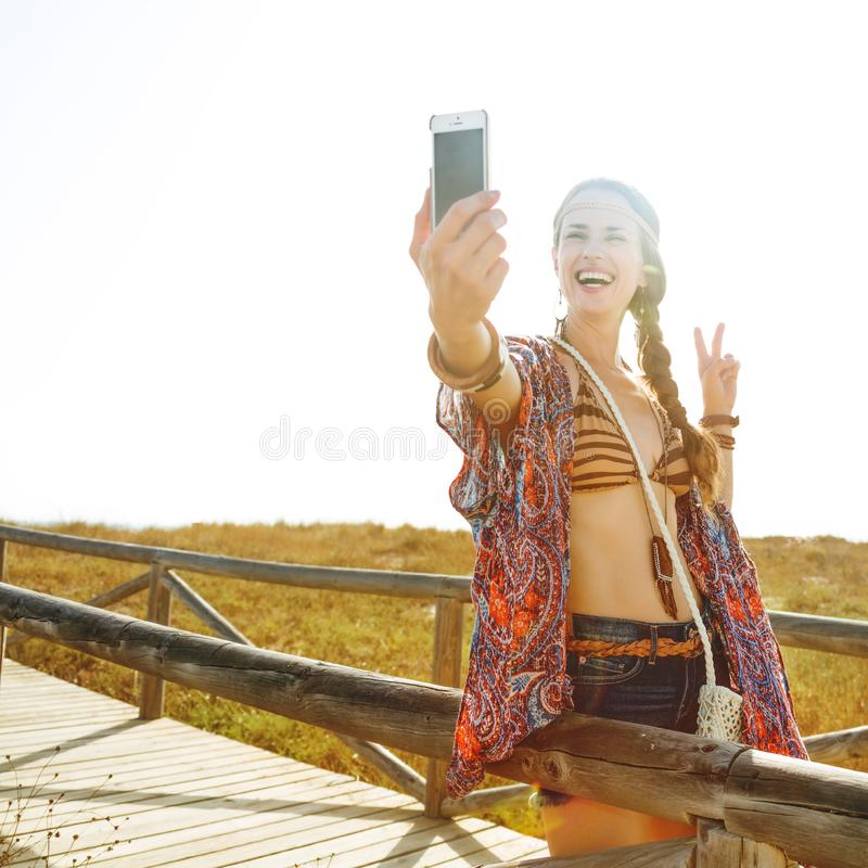 Free spirit girl taking selfie with smartphone and showing victory gesture. Bohemian vibe vacation. smiling modern free spirit girl in jeans shorts and cape stock image