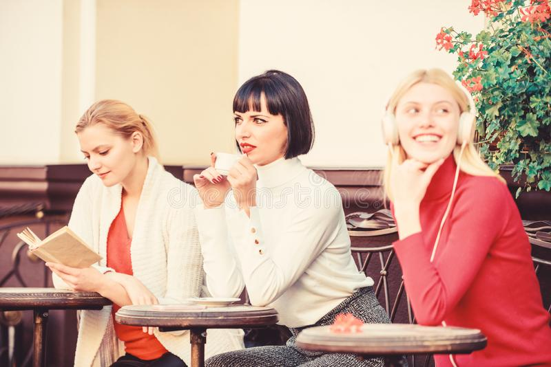 Free time spending. relax. business meeting. three girls do different things. different ways to relax. girls in cafe royalty free stock images