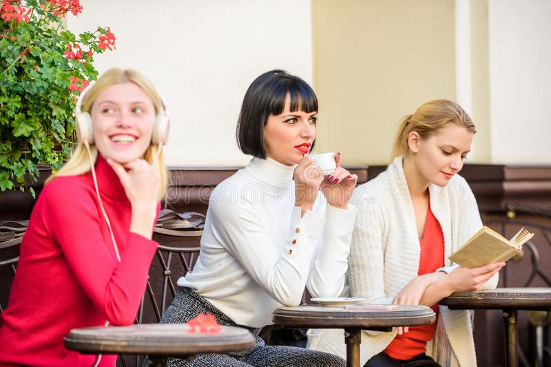Free time spending. relax. business meeting. three girls do different things. different ways to relax. girls in cafe royalty free stock photos