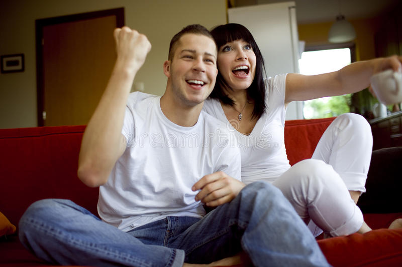 Free time together at home. Man and woman watching tv together stock photography