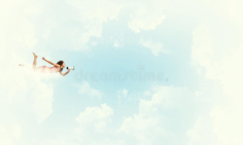 She is free to express herself. Young woman with megaphone flying high in sky royalty free stock photo