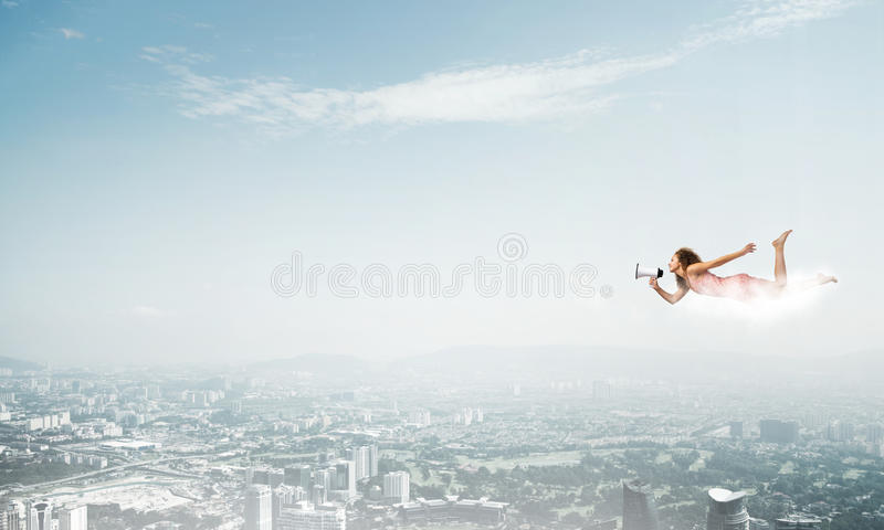 She is free to express herself. Young woman with megaphone flying high in sky stock image