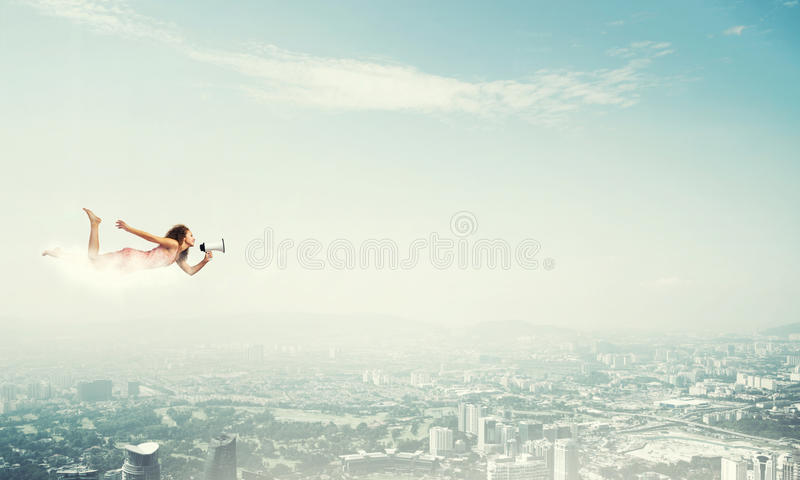 She is free to express herself. Young woman with megaphone flying high in sky royalty free stock image