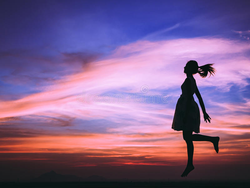 Free woman enjoying and happy. Silhouette of free woman enjoying freedom feeling happy at sunset. relaxing woman in pure happiness stock photography