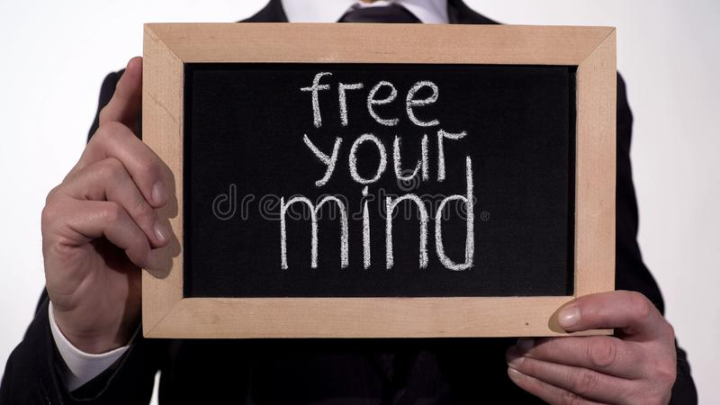 Free your mind phrase on blackboard in businessman hands, creative approach royalty free stock image
