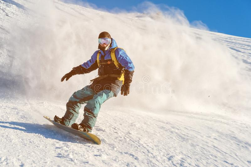 Freeride snowboarder rolls on a snow-covered slope leaving behind a snow powder against the blue sky stock photography