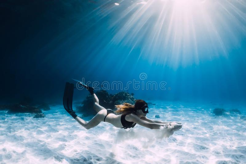 Freediver della donna con la sabbia bianca sopra il mare sabbioso con le alette Freediving subacqueo fotografia stock