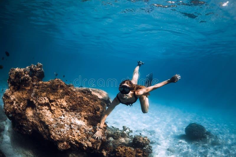 Freediver della donna con le alette ed i coralli Freediving subacqueo in oceano immagine stock libera da diritti