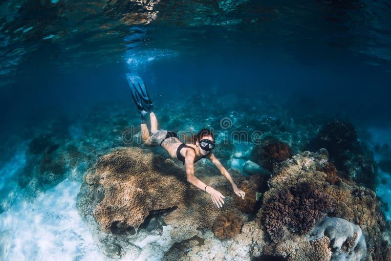 Freediver della donna con le alette ed i coralli Freediving subacqueo in oceano fotografia stock libera da diritti