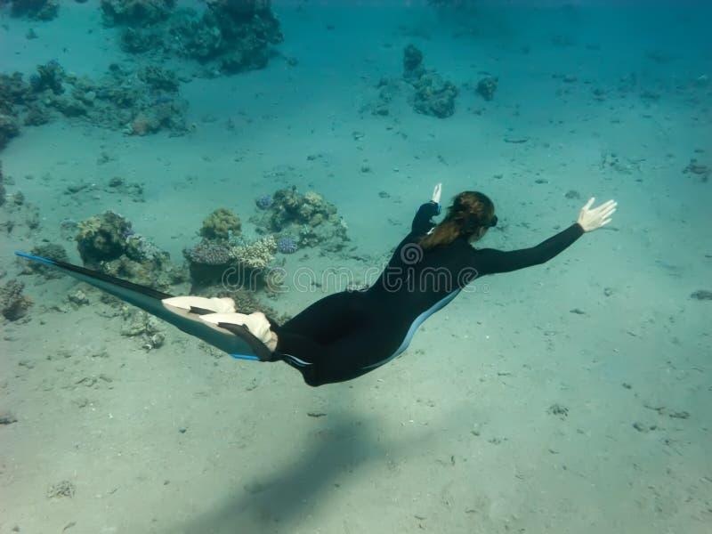 The Freediver Girl Swims Along Sand Sea Bottom Stock Photo