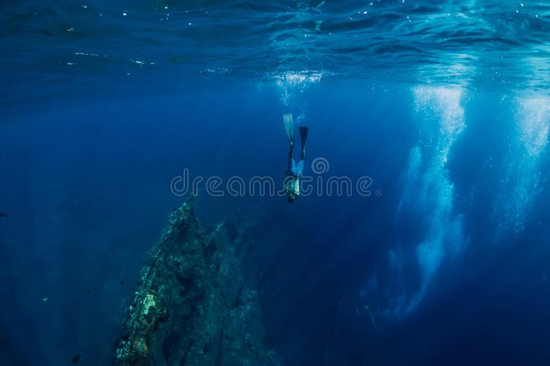 Freediver man dive underwater at shipwreck in Bali. stock image