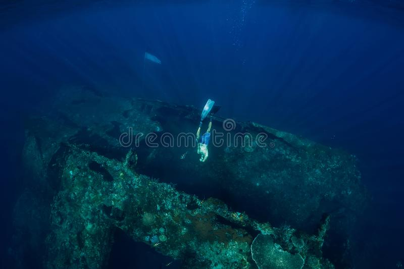 Freediver man dive underwater at shipwreck. Freediving in ocean stock image