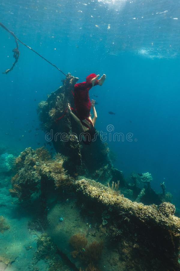 Freediver in rode kleding onderzoekt het schip in de Caraïben royalty-vrije stock afbeeldingen