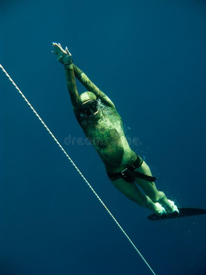 Freediver steigt oben nahe dem Sicherheitsseil lizenzfreie stockbilder