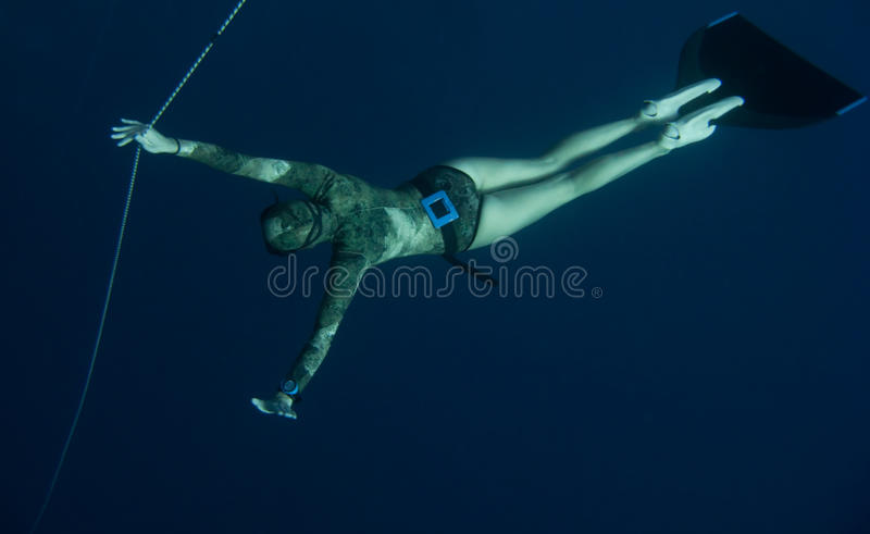Freediver is waiting for someone in the depth stock photo