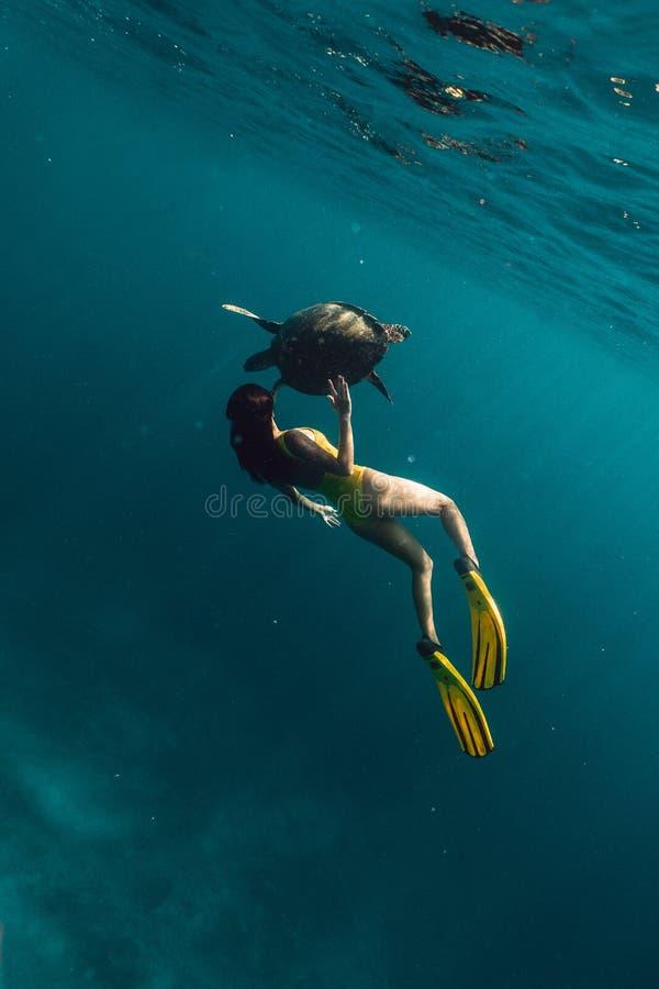 Freediving caucasiano da menina subaquático com a tartaruga bonita no mar azul imagem de stock royalty free