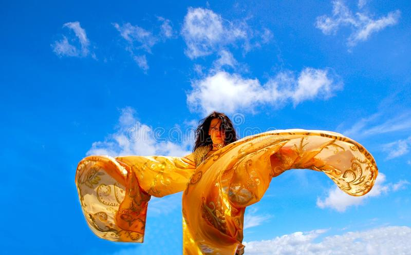 Freedom. A beautiful Caucasian dancing woman with golden moving shawl wings in front of blue sky background