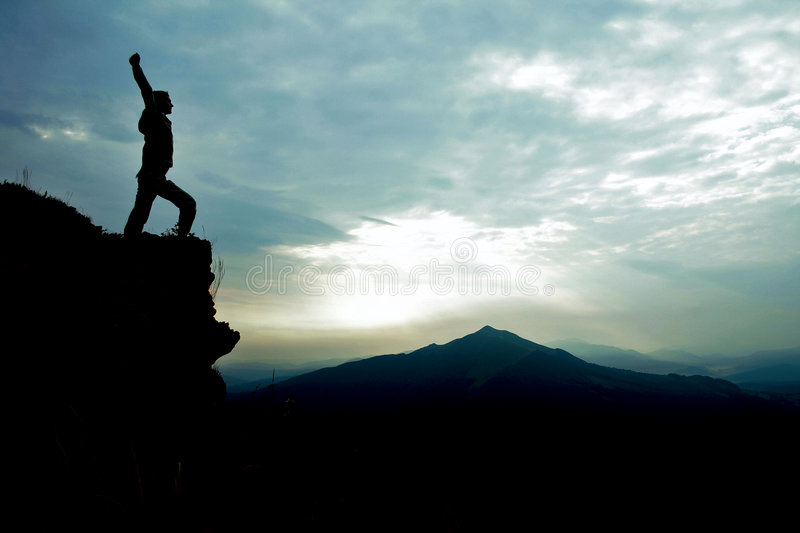 Man on top of cliff with arms raised royalty free stock photography