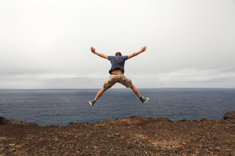Freedom or adventure concept - jump of young man stock images