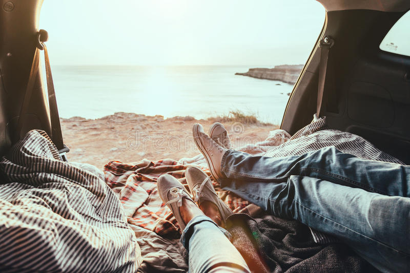 Freedom car travel concept. Man and woman relaxing inside trunk and watching at the sea. Fall car trip in sunset. Freedom travel concept. Autumn weekend royalty free stock photo
