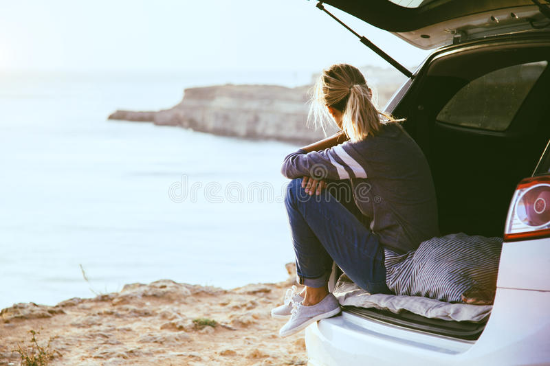 Freedom car travel concept. Woman relaxing inside car trunk and watching on sea. Fall trip in sunset. Freedom travel concept. Autumn weekend royalty free stock photo
