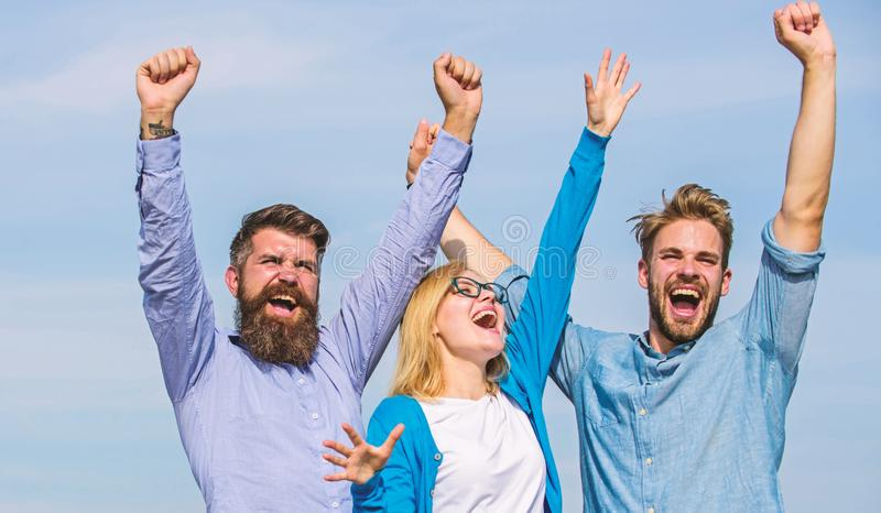 Freedom concept. Company three happy colleagues office workers enjoy freedom, sky background. Employees enjoy feeling of stock image