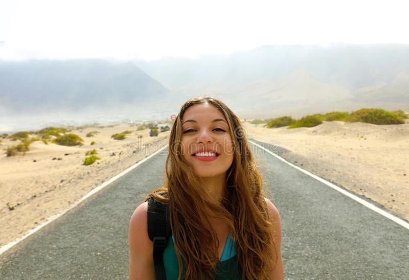 Freedom concept. Portrait of young woman in the middle of desert asphalt road highway in Lanzarote Island, Spain stock photo