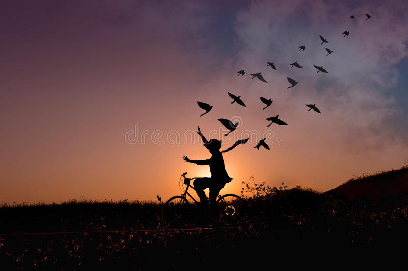 Freedom concept, Silhouette of happy person raised arms on bicycle in natural scene, Birds fly on beautiful sunrise or sunset sky royalty free stock photos