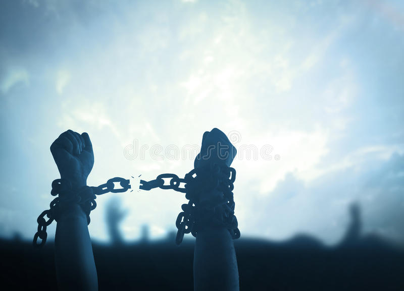 International human rights day concept. Silhouette human hands raising and broken chains at night background royalty free stock photos