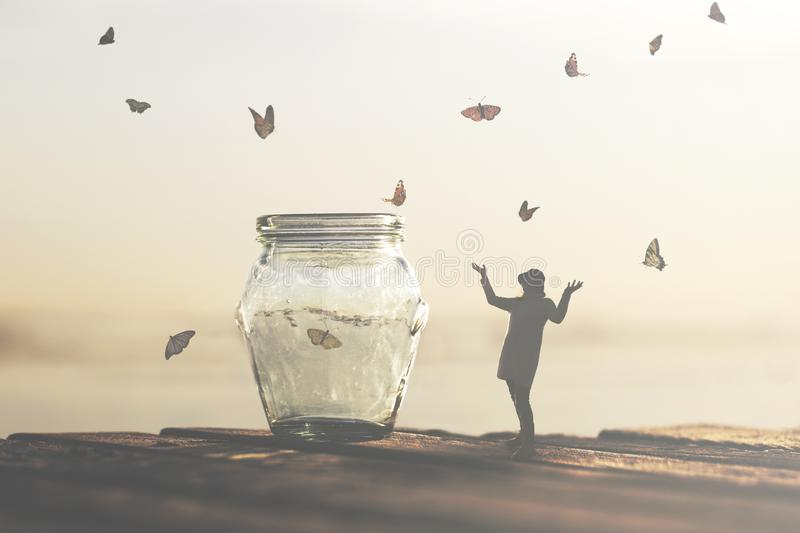 Freedom concept of woman saving captive butterflies in a vase stock images