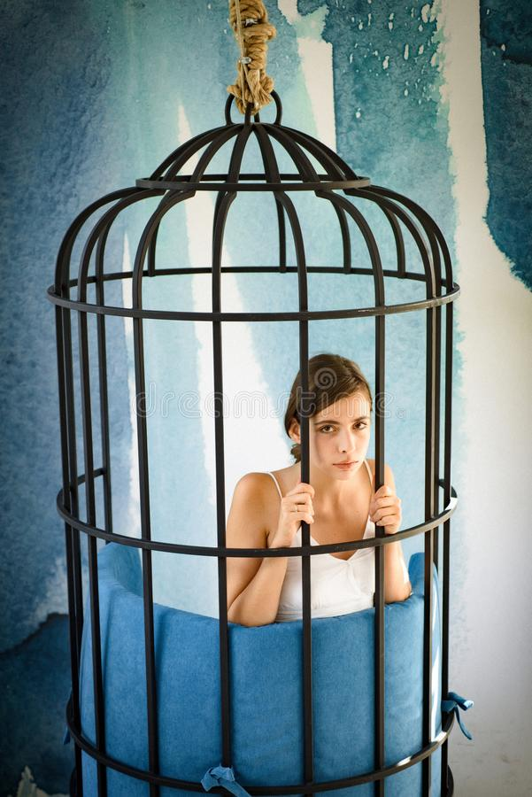 Freedom of cute girl in cage. got something on her mind. woman in iron cage. fashion slave in captivity of beauty stock photos