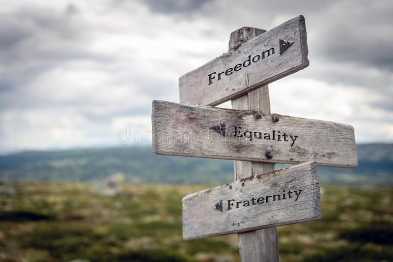 Freedom, equality and fraternity text on wooden sign post outdoors in landscape scenery. stock image