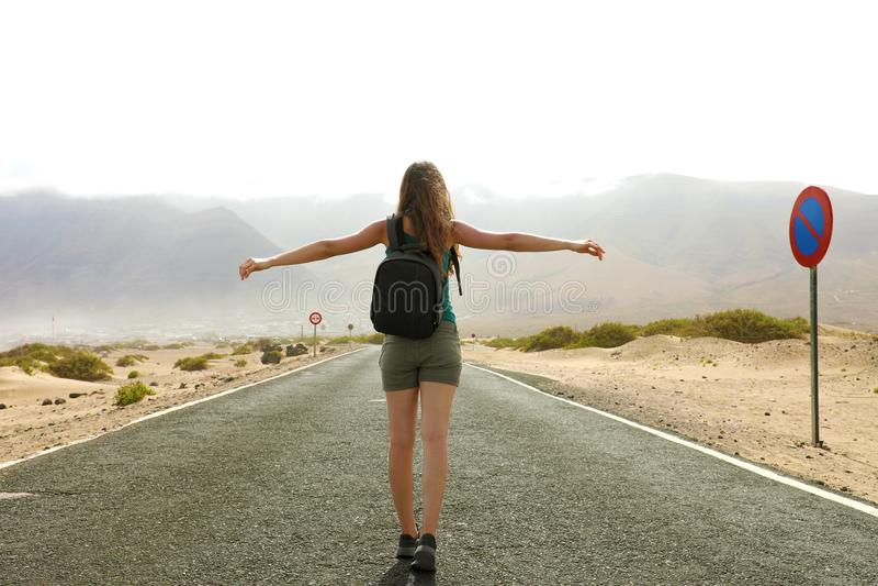 Freedom flying woman in free happiness bliss in empty asphalt desert road. Happy female traveler backpacker enjoying silence royalty free stock images