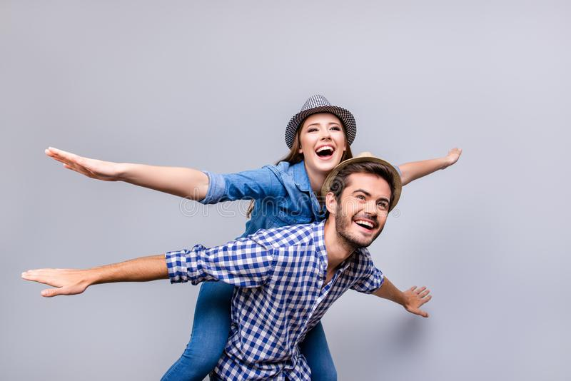 Freedom and fun, emotions and feelings. Cheerful and playful couple in casual outfits and hats are fooling around, gesturing plan. E wings, smiling, posing stock image