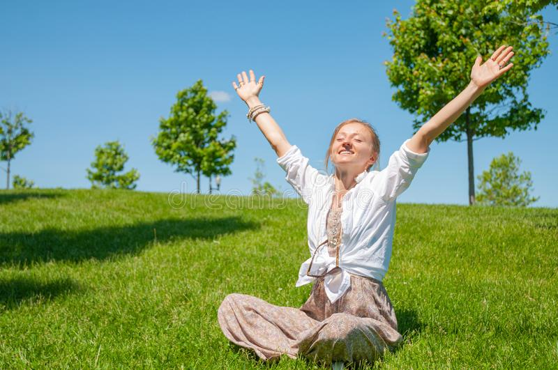 Freedom and happiness concept. Beautiful woman with raising up her hands is sitting on grass, enjoy sunny day royalty free stock photos