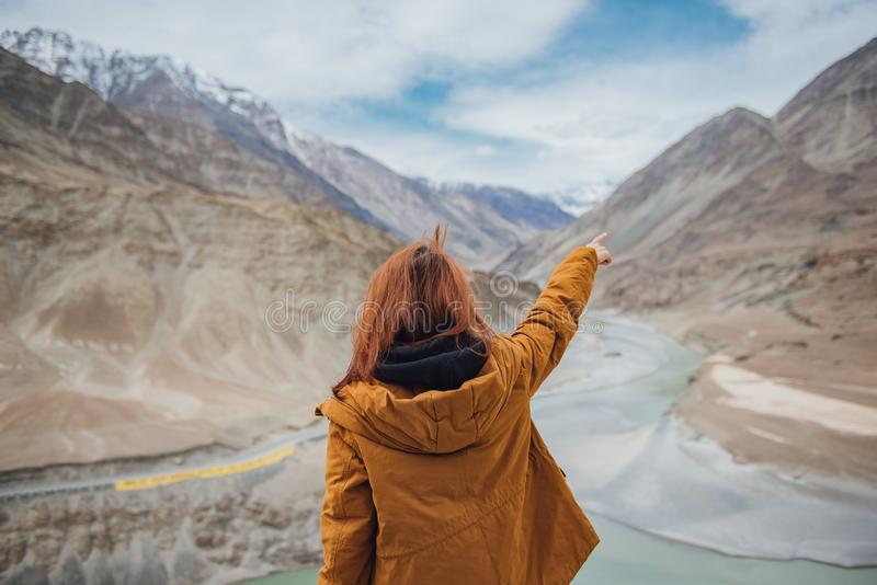 Happy young woman traveler pointing to the mountain enjoy the beautiful view at confluence of zanskar and indus rivers in leh. royalty free stock photography
