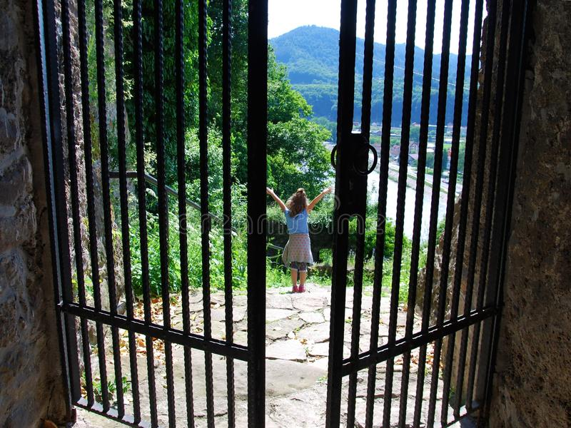 Freedom: happiness. Little girl opened her arms in front of the iron gate; freedom or happiness concept royalty free stock image