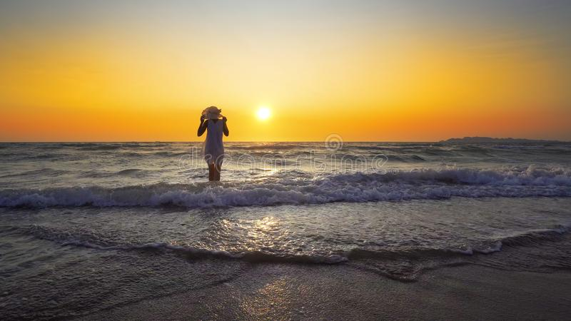 Freedom and happiness woman on beach at sunse. Smile Freedom and happiness woman on beach at sunset. She is enjoying serene ocean nature during travel holidays royalty free stock photo