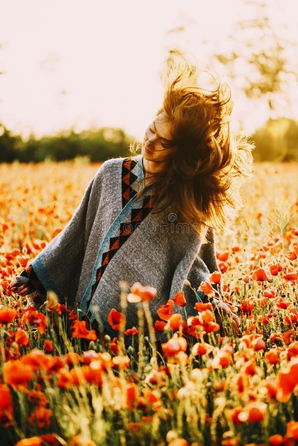 Happy beautiful woman relaxing in poppy flower field. royalty free stock photography