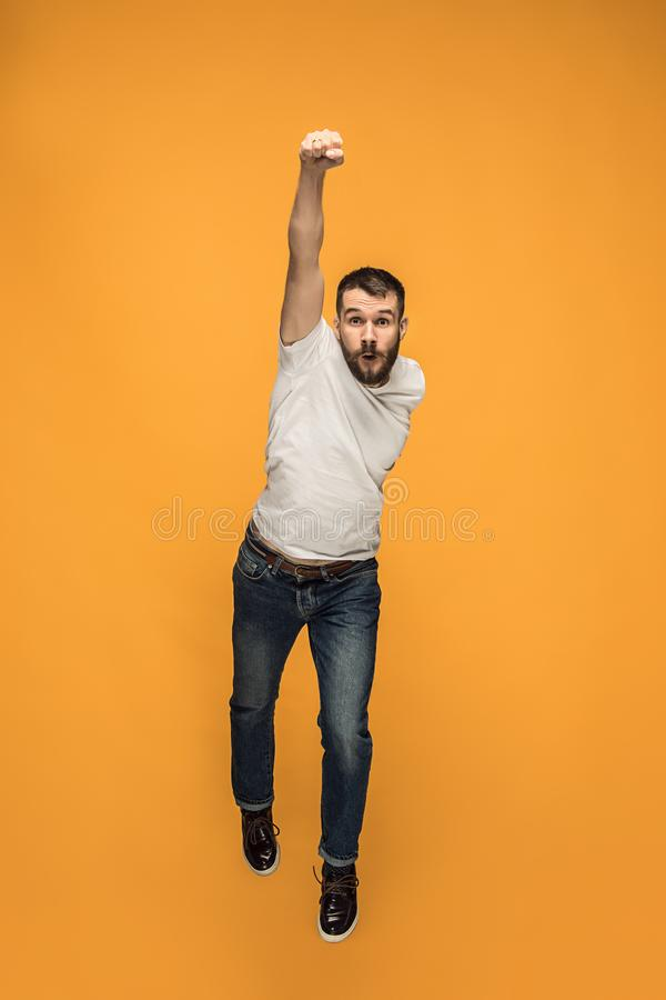 Freedom in moving. handsome young man jumping against orange background royalty free stock photos
