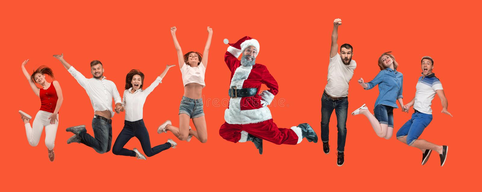Freedom in moving. young man and women jumping against red background royalty free stock image