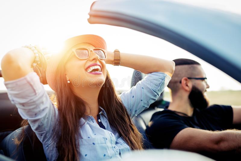 Freedom of the open road.Young Couple Driving Along Country Road In Open Top Car royalty free stock photography