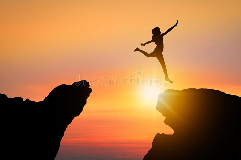 freedom and possible concept, silhouette people jumping over rock mountain successfully royalty free stock photos
