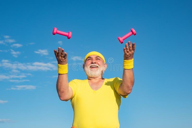 Freedom retirement concept. Portrait of healthy happy smile senior. Health club or rehabilitation center for elderly. Aged pensioner. Senior sport man lifting stock photos
