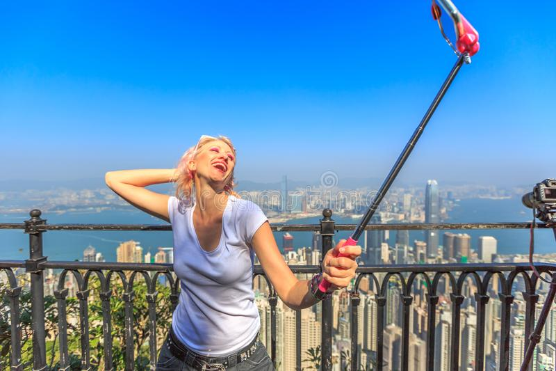 Freedom tourist at Victoria Peak. Hong Kong Victoria Peak tourist taking selfie stick picture photo with smartphone enjoying view over Victoria Harbour from stock photography