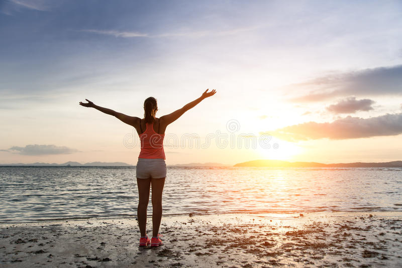 Freedom and tranquility at the beach on sunset. Sporty woman enjoying relax and freedom towards the sun and sea on sunset at the beach. Tranquility and bliss royalty free stock photography