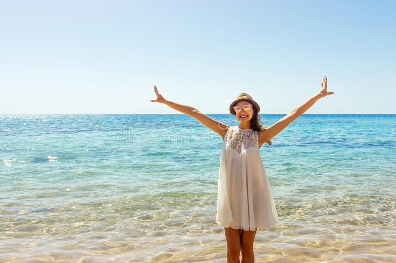 Freedom woman in free happiness bliss on beach. Smiling happy girl in white summer dress in vacation outdoors.  stock photos