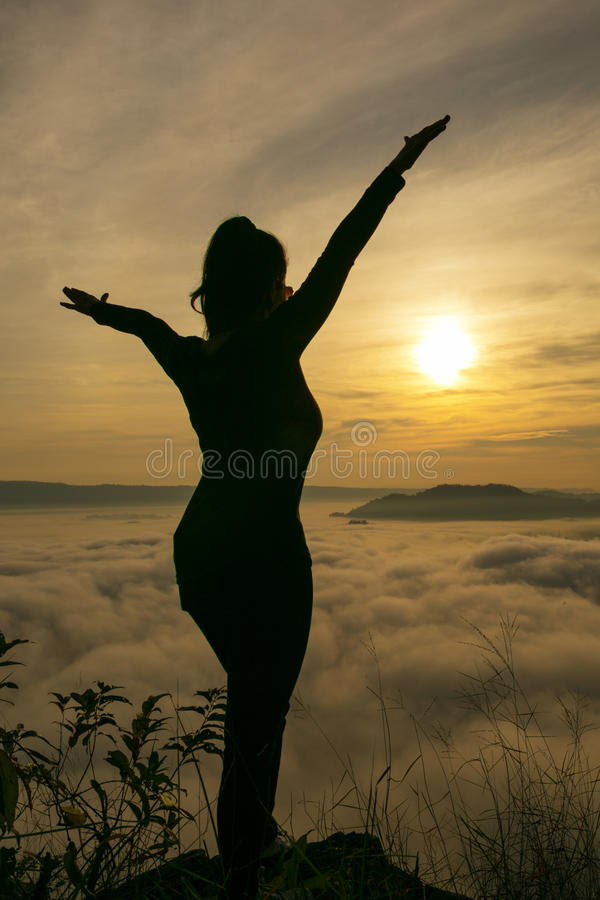 Freedom of women. Freedom of woman Standing on the mountain mist into the foreground stock images