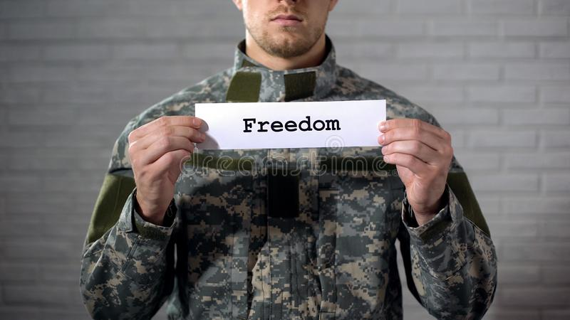 Freedom word written on sign in hands of male soldier, peace, end of war stock image